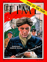 Time magazine cover depicting an armed male with unruly hair and a determined look on his face, wearing a blue coat, a green scarf and gloves with the fingertips cut out. A Hungarian flag with a circle cut out of its midddle is in the background