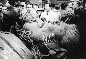 "A group of 17 civilians behind the head of a fallen bronze statue of Josef Stalin lying face-up, defaced with some graffiti including ""W.C."""